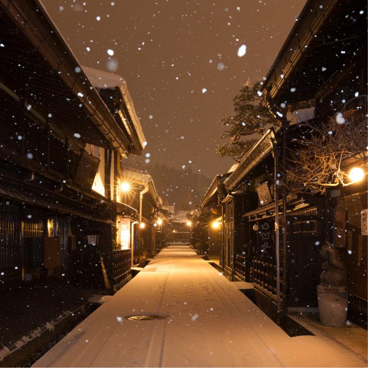 夜の雪の古い町並み